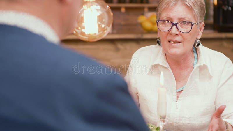 Femme supérieure regardant avec amour son mari pendant le dîner dans un restaurant image libre de droits