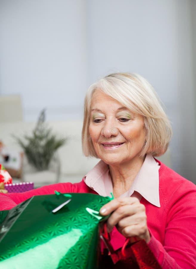Femme supérieure regardant dans le sac image libre de droits