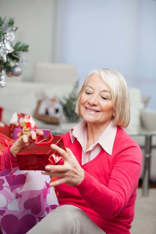 Femme supérieure regardant le cadeau de Noël dans le sac image libre de droits