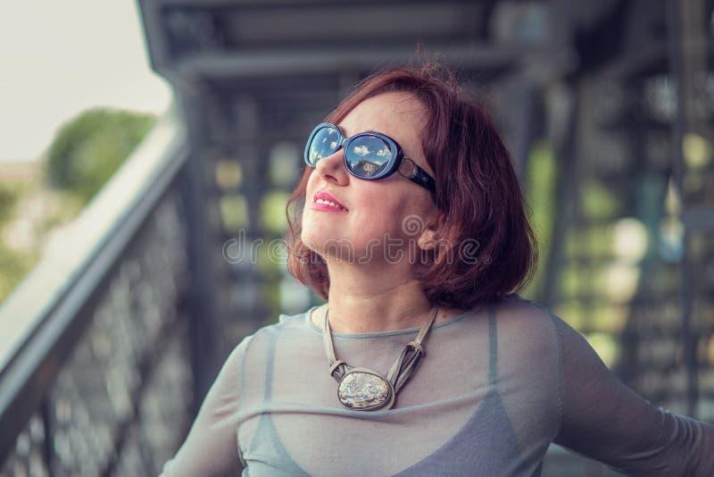 Femme supérieure regardant les lunettes de soleil de port reflétant des nuages et des cieux photos libres de droits