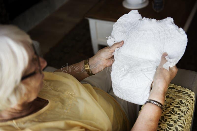 Femme supérieure regardant une couche-culotte images libres de droits