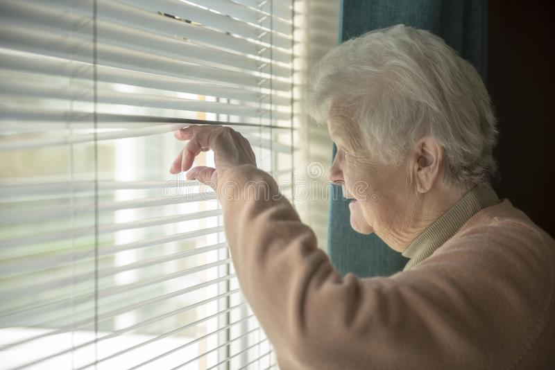 Femme supérieure remarquant par la fenêtre photos libres de droits