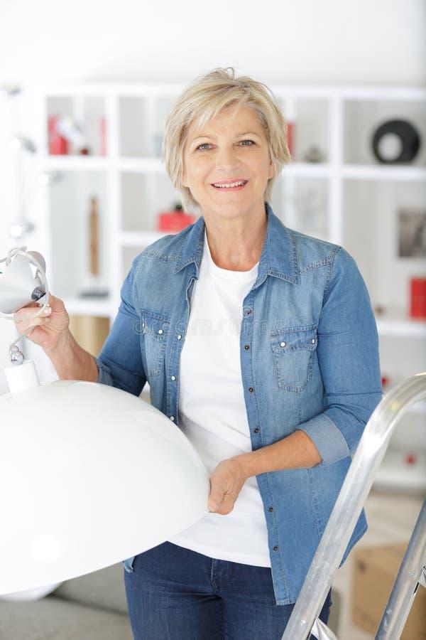 Femme supérieure remplaçant l'ampoule à la maison photographie stock