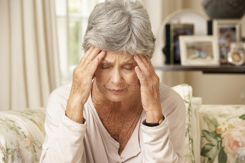 Femme supérieure retirée malheureuse s'asseyant sur Sofa At Home photo stock