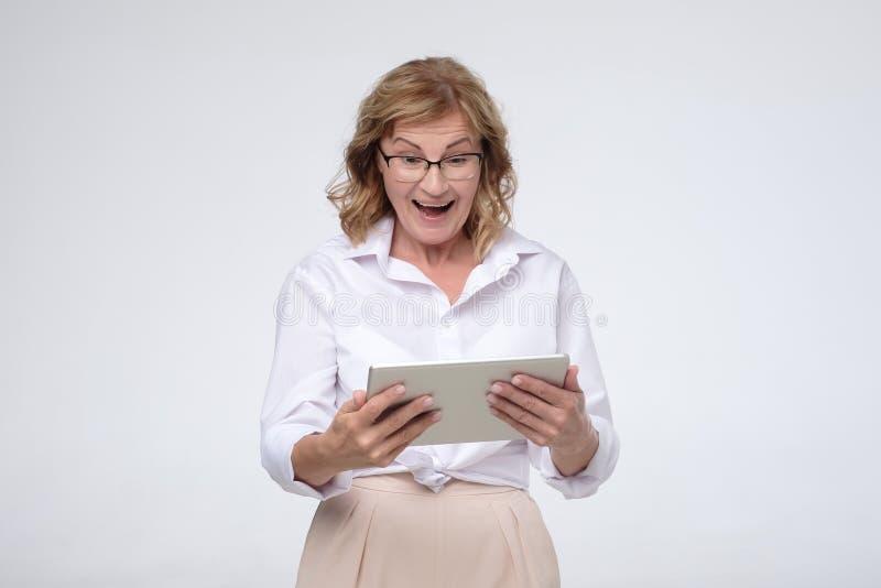 Femme supérieure riante à l'aide de la tablette pour acheter une certaine substance images stock