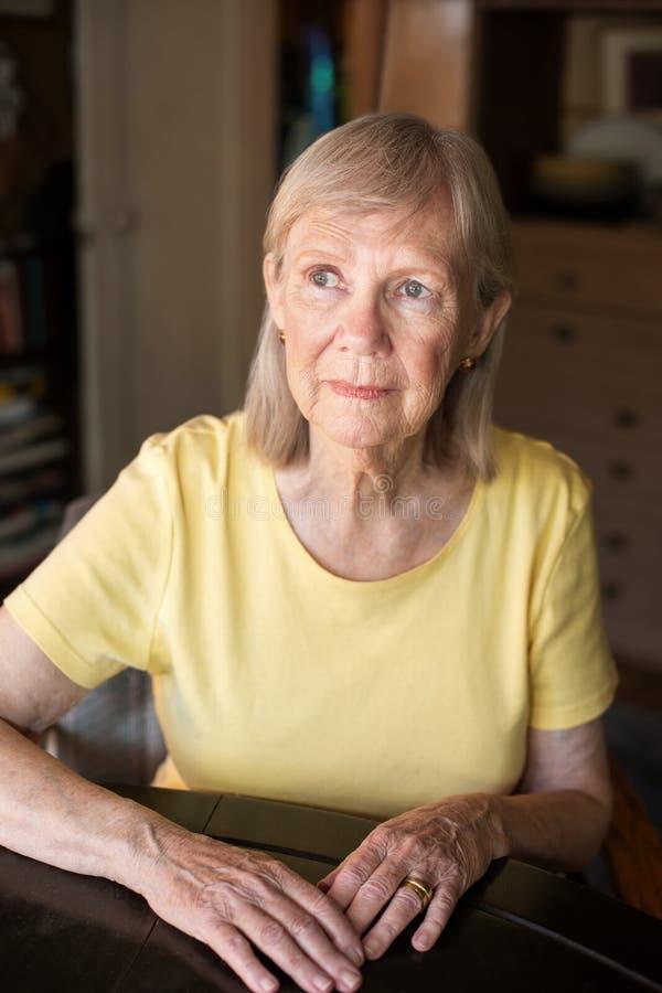 Femme supérieure sérieuse assise à la table photographie stock libre de droits