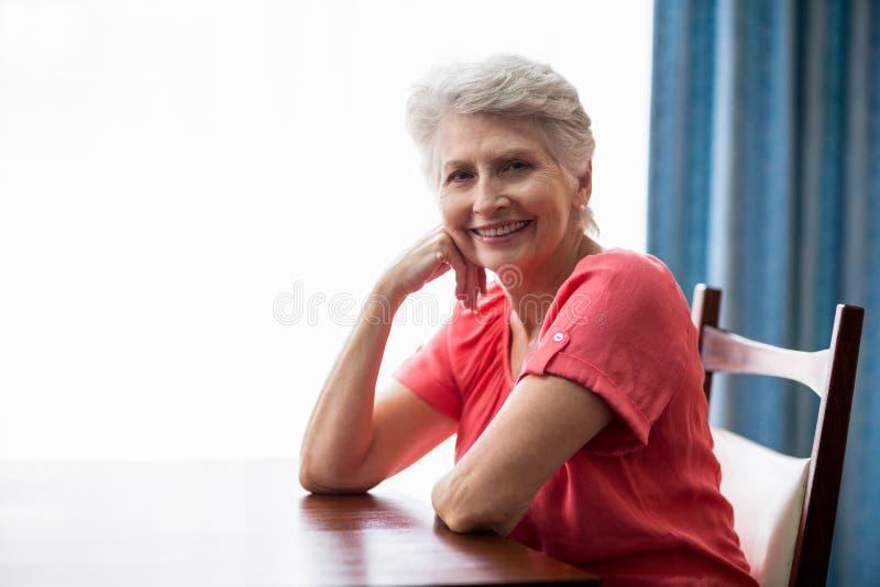 Femme supérieure s'asseyant à une table photographie stock libre de droits