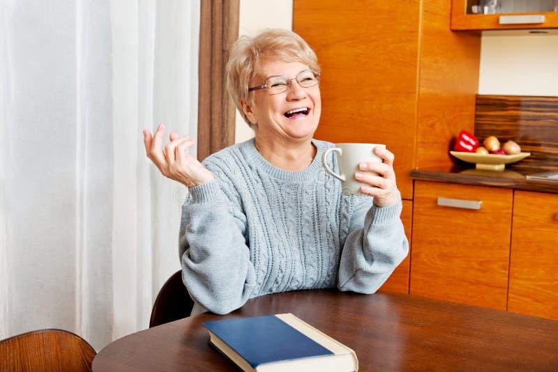 Femme supérieure s'asseyant au bureau avec le livre et le thé ou le café potable image libre de droits