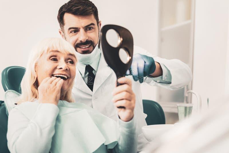 Femme supérieure s'asseyant dans la chaise dentaire et regardant le miroir photos libres de droits