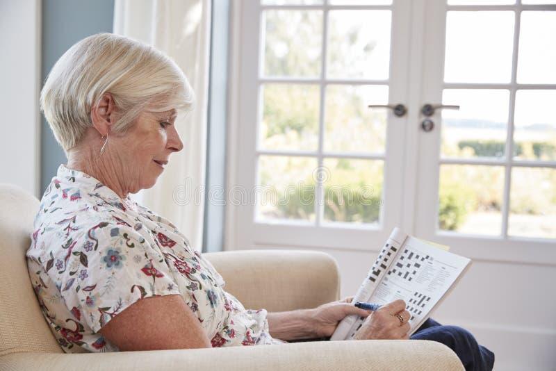 Femme supérieure s'asseyant dans le fauteuil faisant des mots croisé à la maison images libres de droits