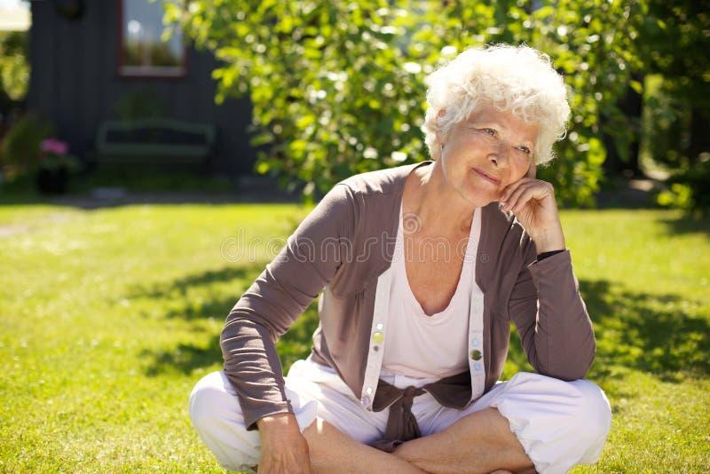 Femme supérieure s'asseyant dehors perdu dans les pensées images libres de droits