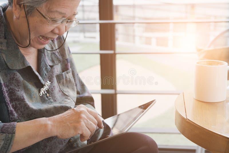 Femme supérieure s'asseyant et se reposant dans le café de café utilisant le chiffre photos stock