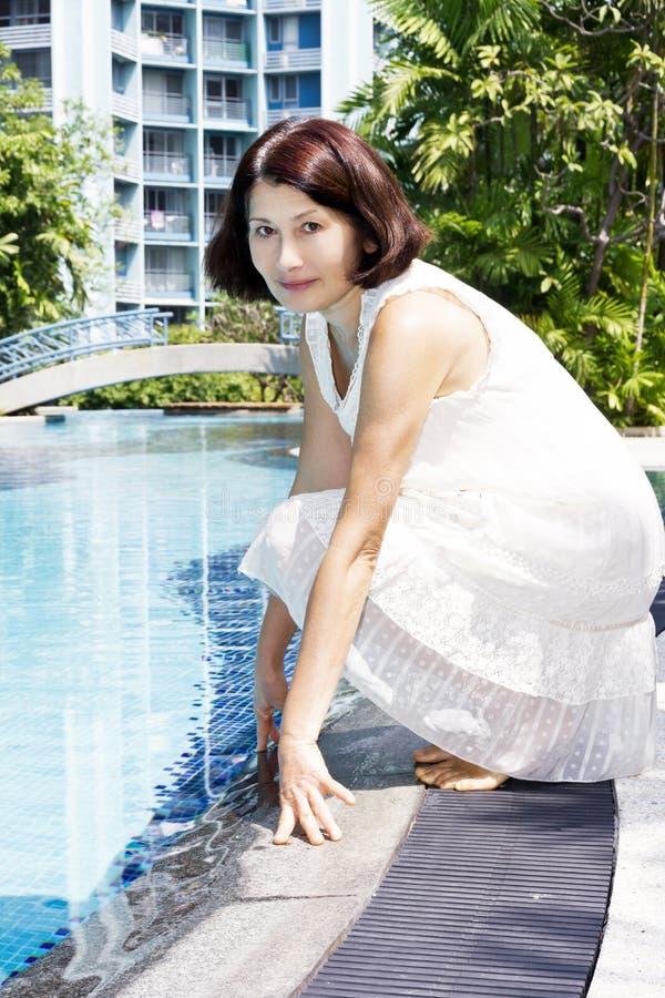 Femme supérieure s'asseyant par la piscine photo libre de droits