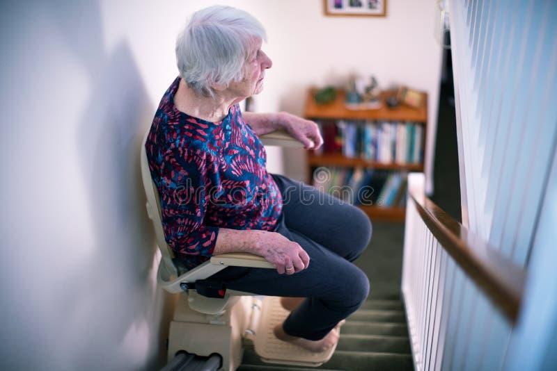 Femme supérieure s'asseyant sur l'ascenseur d'escalier à la maison pour aider la mobilité images libres de droits