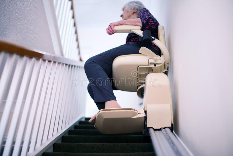 Femme supérieure s'asseyant sur l'ascenseur d'escalier à la maison pour aider la mobilité image libre de droits