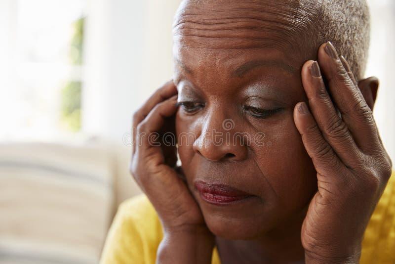 Femme supérieure s'asseyant sur la dépression de Sofa At Home Suffering From photos libres de droits