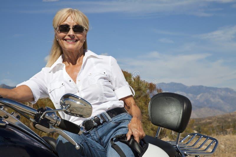 Femme supérieure s'asseyant sur la moto sur la route de désert photographie stock libre de droits