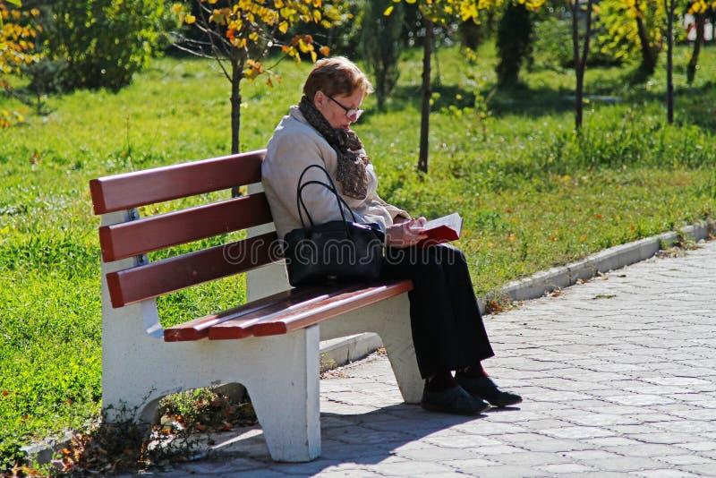 Femme supérieure s'asseyant sur le banc en bois et lisant un livre en parc à Volgograd photographie stock libre de droits