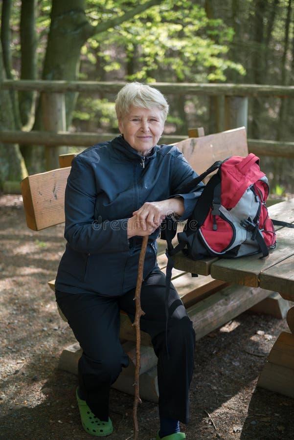 Femme supérieure s'asseyant sur un banc images libres de droits