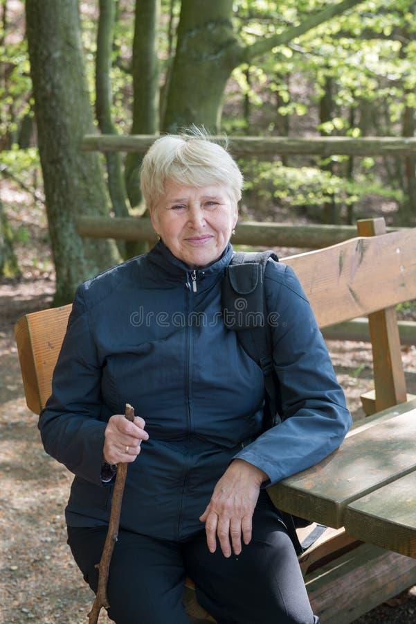 Femme supérieure s'asseyant sur un banc photographie stock