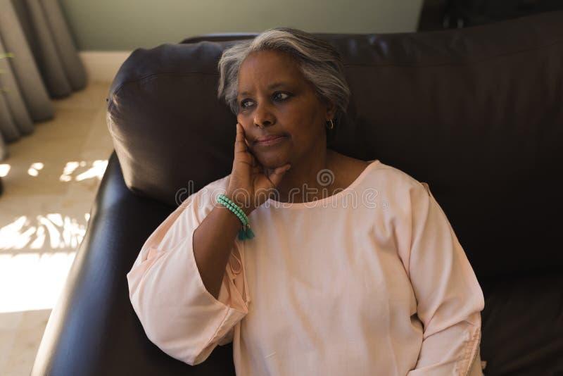 Femme supérieure s'asseyant sur un sofa dans le salon à la maison photographie stock libre de droits