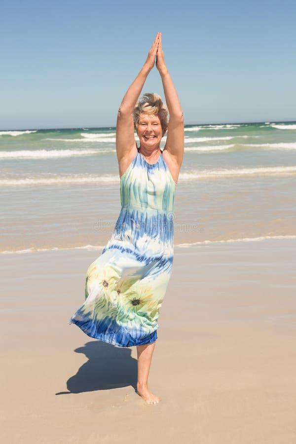 Femme supérieure s'exerçant tout en se tenant à la plage photo stock