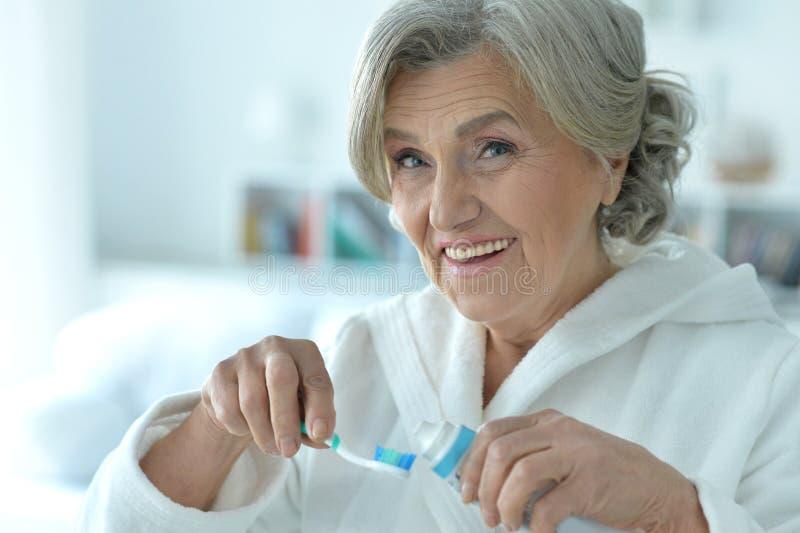 Femme supérieure se brossant les dents images libres de droits