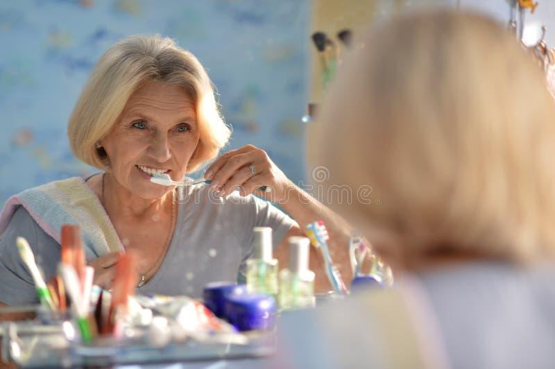 Femme supérieure se brossant les dents photographie stock