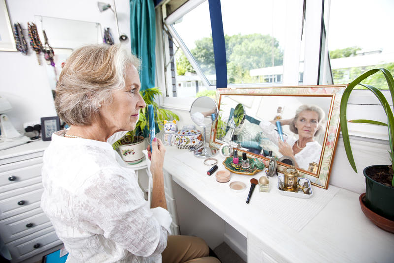 Femme supérieure se peignant les cheveux à la raboteuse dans la maison images stock