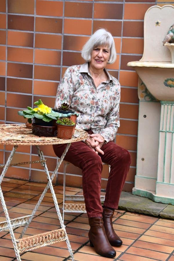 Femme supérieure se reposant dans son jardin sur sa terrasse photo stock