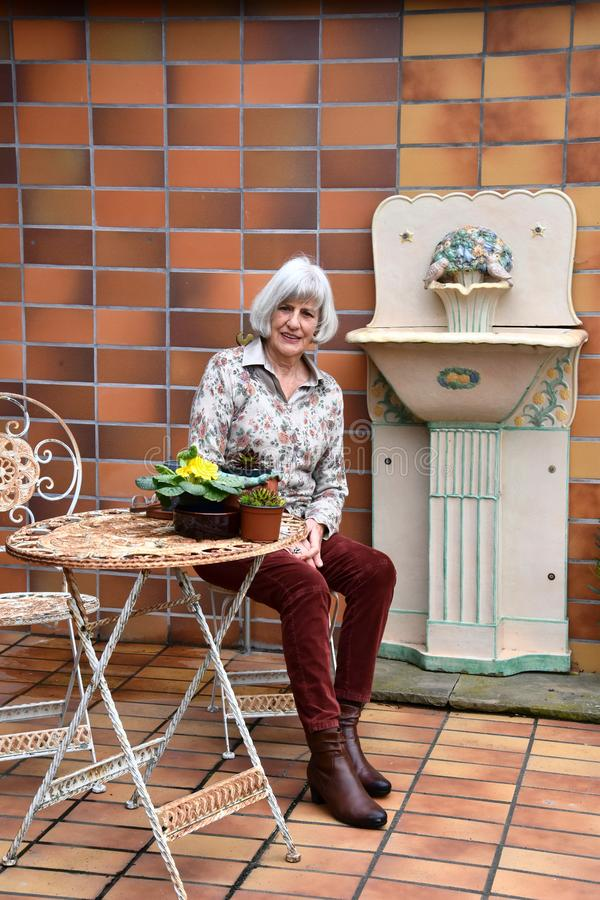 Femme supérieure se reposant dans son jardin sur sa terrasse photographie stock libre de droits