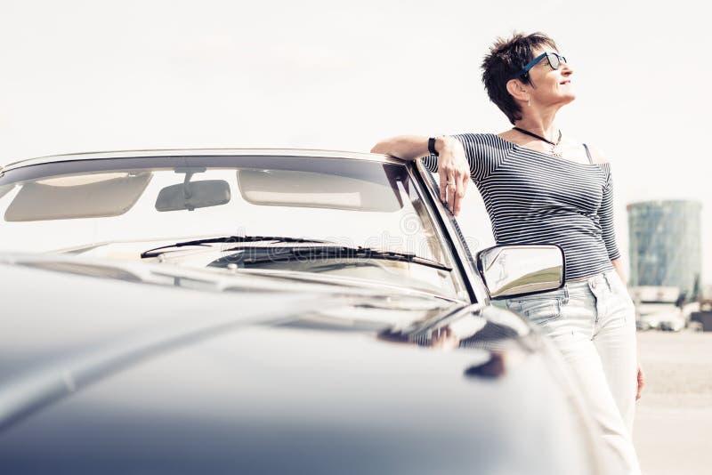 Femme supérieure se tenant à côté de la voiture classique convertible photo libre de droits