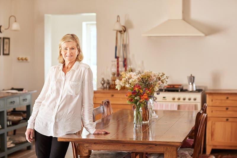Femme supérieure se tenant dans une cuisine rangée de style rustique photos libres de droits