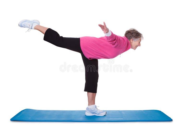 Femme supérieure se tenant sur un jambe et exercice photographie stock