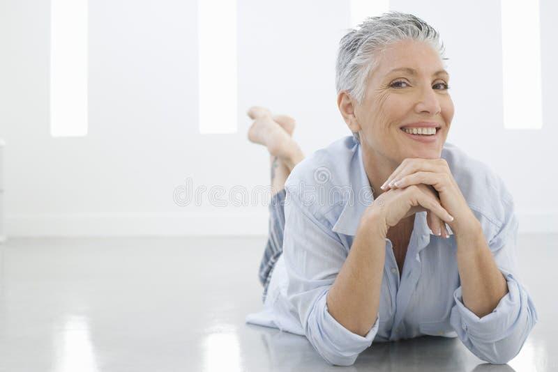 Femme supérieure se trouvant sur le plancher photographie stock