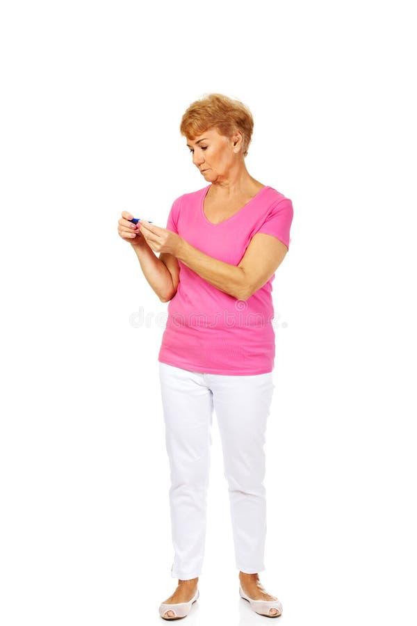 Femme supérieure songeuse tenant le thermomètre photos stock