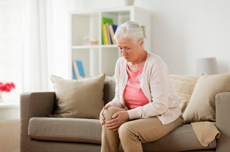 Femme supérieure souffrant de la douleur dans la jambe à la maison photo libre de droits