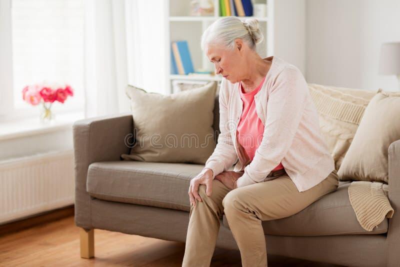 Femme supérieure souffrant de la douleur dans la jambe à la maison photos stock