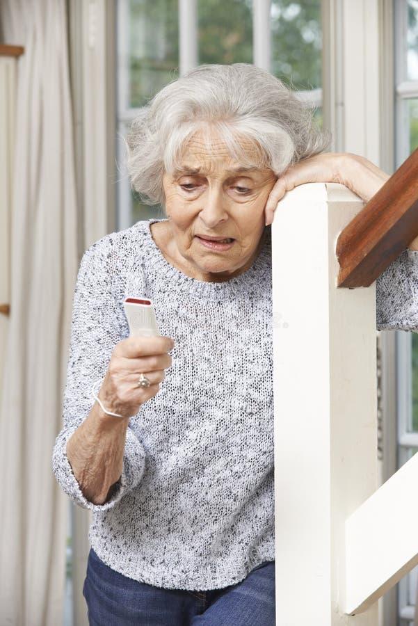 Femme supérieure souffrante employant l'alarme personnelle à la maison images stock
