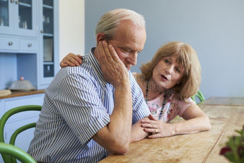 Femme supérieure soulageant l'homme avec la dépression à la maison images stock