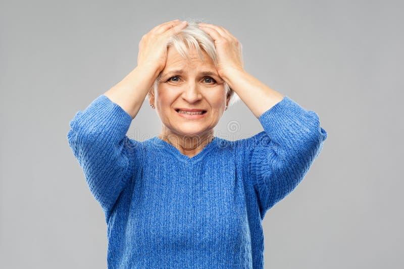 Femme supérieure soumise à une contrainte se tenant sur sa tête photographie stock