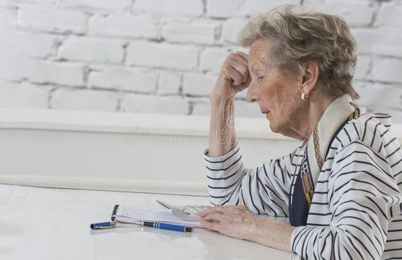 Femme supérieure soumise à une contrainte vérifiant le financee avec la calculatrice à la maison photo libre de droits