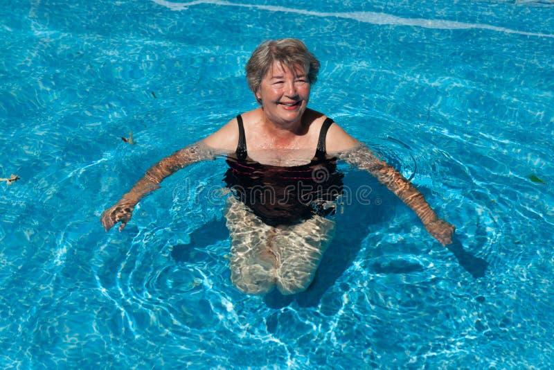 Femme supérieure souriant dans une piscine image libre de droits