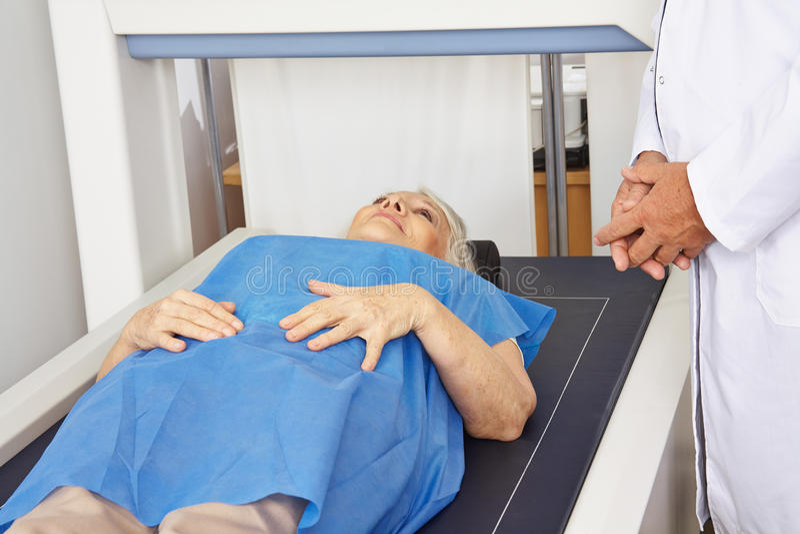 Femme supérieure sous la machine pour la mesure de densité d'os photos libres de droits