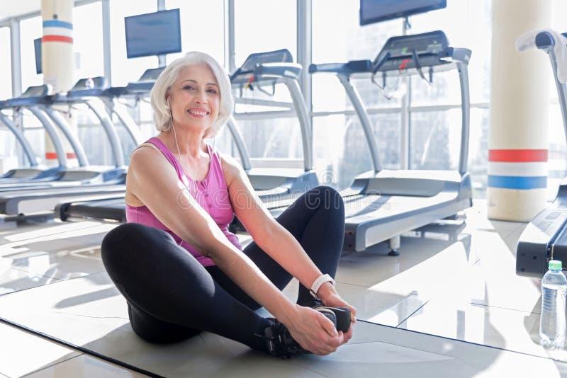 Femme supérieure sportive de sourire faisant des exercices dans un gymnase photographie stock libre de droits