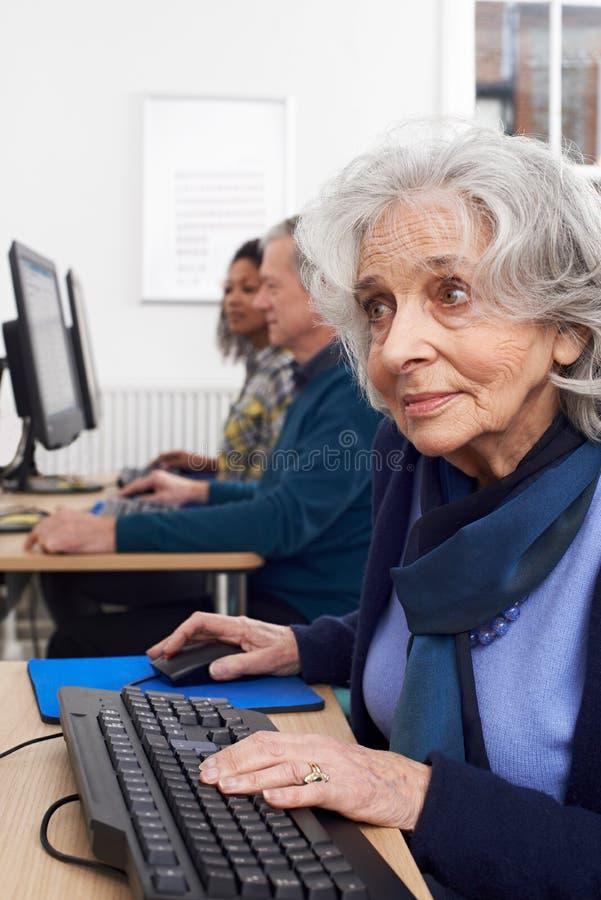 Femme supérieure suivant la classe d'ordinateur image stock