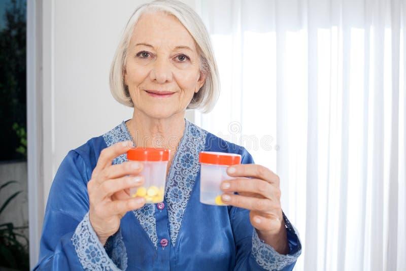 Femme supérieure tenant des bouteilles de pilule à la maison de repos photos stock