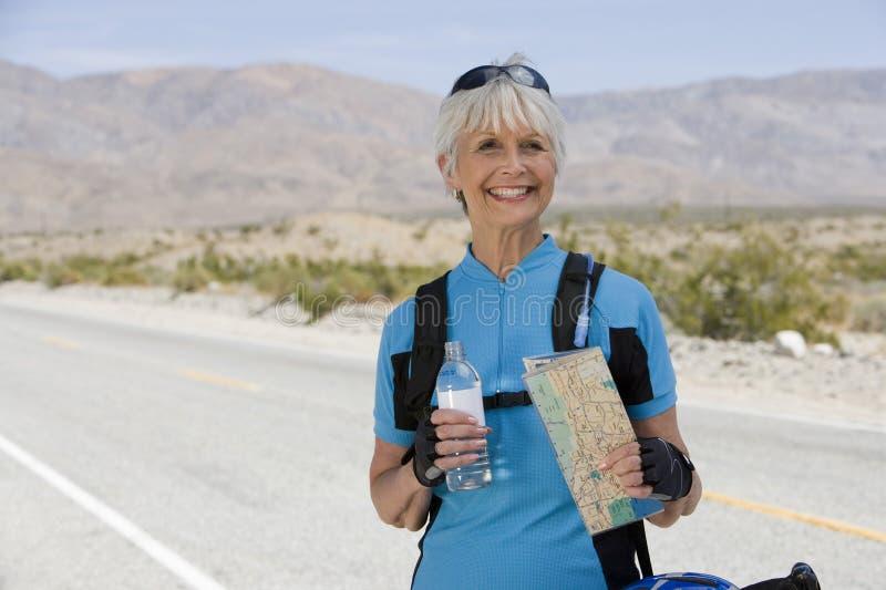 Femme supérieure tenant la carte et la bouteille de l'eau photo libre de droits