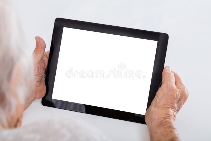Femme supérieure tenant la Tablette de Digital photos stock