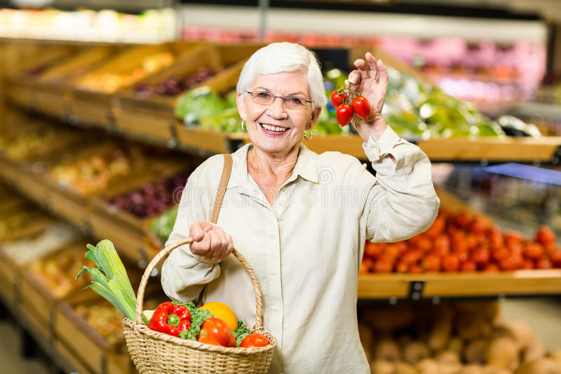 Femme supérieure tenant le panier et les petites tomates images stock